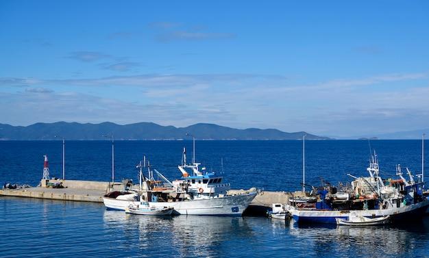Łodzie w porcie nea roda na błękitnej wodzie morskiej, halkidiki, grecja