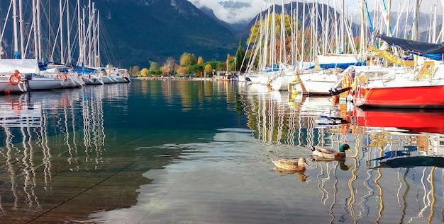 Łodzie zaparkowane przy jachtach żaglowych cumują jesienią przy górskich łódkach