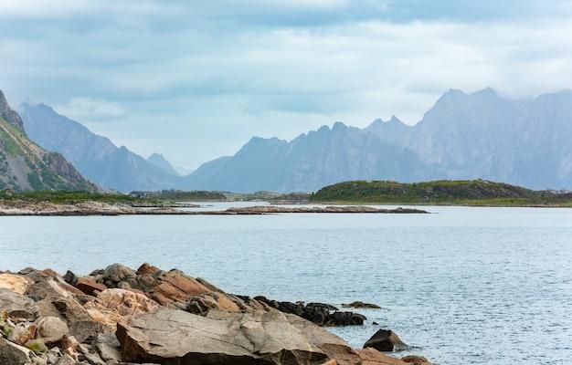 Lofoty kamienisty fiord i góry pochmurny krajobraz lato, norwegia.