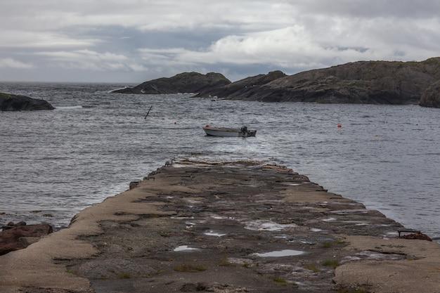 Lofoty, norwegia - 20 czerwca 2017 r .: łódź rybacka na wodzie norweskich fiordów w pochmurny dzień