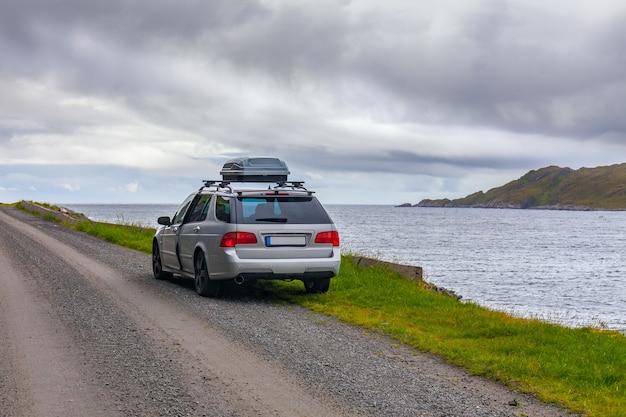 Lofoty, norwegia - 20 czerwca 2017: szary samochód zaparkowany na brzegu norweskiego fiordu
