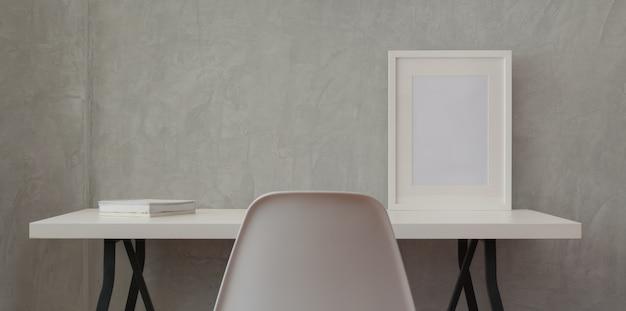 Loftowe miejsce pracy z białym drewnianym biurkiem i ramą makiety oraz białą książką w szarej ścianie