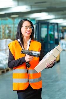 Logistyka - pracownica lub spedytor z kamizelką ochronną i skanerem, skanuje kod kreskowy paczki, stoi w magazynie firmy spedycyjnej