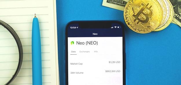 Logo i symbol waluty kryptograficznej neo na ekranie nowoczesnego telefonu komórkowego, zdjęcie w tle banera finansów firmy