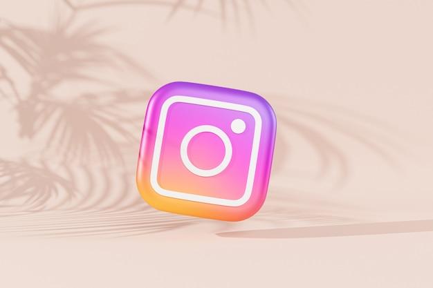 Logo instagrama na beżowej powierzchni z cieniami tropikalnych liści