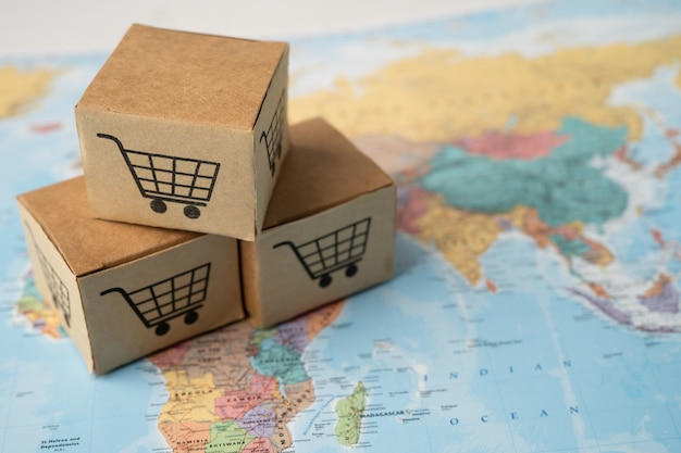Logo koszyka na zakupy na pudełku na mapie świata