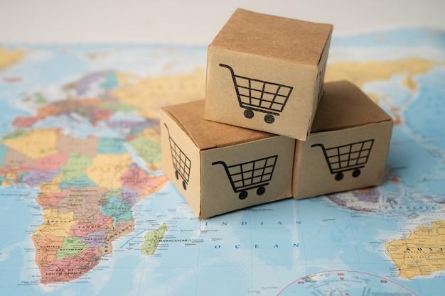 Logo koszyka na zakupy na pudełku na tle mapy świata