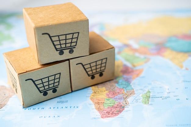 Logo koszyka na zakupy na pudełku na tle mapy świata.