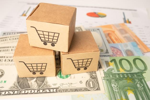 Logo koszyka na zakupy na pudełku z tłem banknotów euro i dolara amerykańskiego.