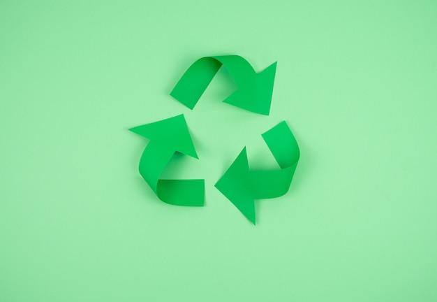 Logo recyklingu na zielonym papierze.