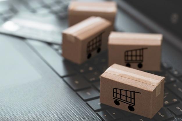 Logo wózka lub wózka na zakupy na małych pudełkach kartonowych i karcie kredytowej leżało na laptopie z klawiaturą do zakupów online i świadczenia usług zgodnie z koncepcją klienta.