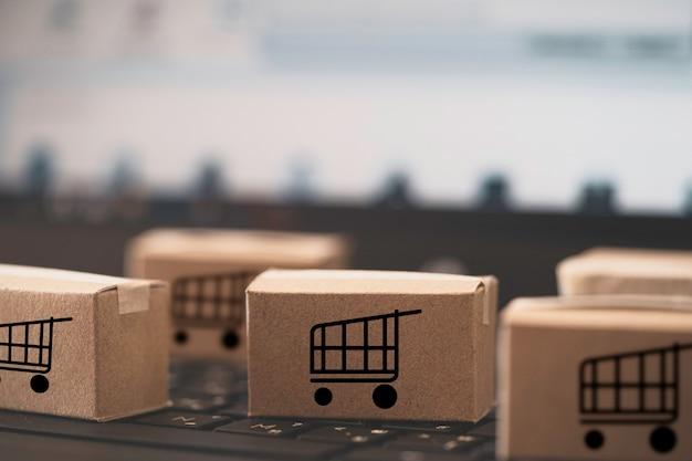 Logo wózka lub wózka na zakupy na małych pudełkach kartonowych leżało na laptopie z klawiaturą do zakupów online i dostarczania usług zgodnie z koncepcją klienta.