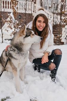 Lojalny pies odwracający wzrok w zimowy dzień, głaszcząc go roześmiana kobieta w białej kurtce. spektakularna europejska dama w dżinsach pozuje z husky na zaśnieżonej ziemi.