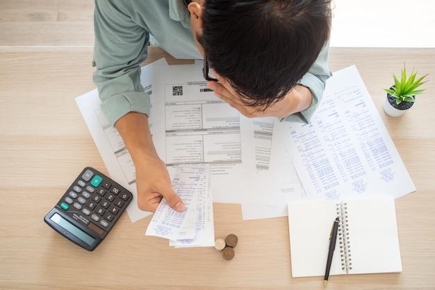 Lokaj zmartwione dłonie dotykają czoła, które ma wiele wydatków, takich jak rachunki za prąd, rachunki za internet, rachunki za telefon komórkowy i rachunki za karty kredytowe, bez pieniędzy do zapłaty. koncepcja długów