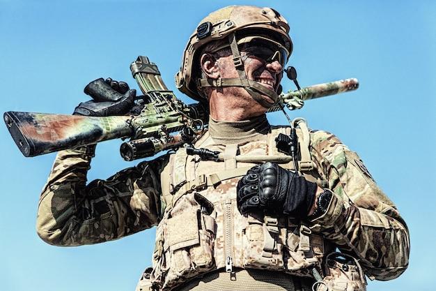 Lokalizacja portret żołnierza sił specjalnych w mundurze polowym z bronią, portret na błękitnym niebie