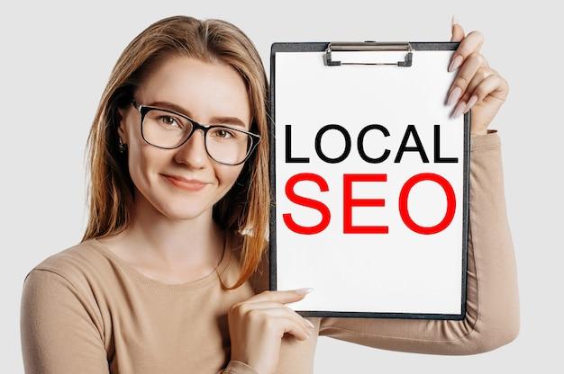 Lokalne seo. piękna młoda biznesowa kobieta w okularach trzyma schowek z makiety miejsca na białym tle na szarym tle