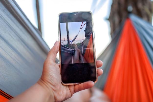 Lokalne wakacje. kobieta odpoczywa w hamaku nad brzegiem morza i robi selfie dla sieci społecznościowej