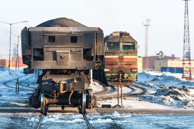 Lokomotywa spalinowa z pociągami towarowymi na stacji kolejowej. tundra polarna, zima.