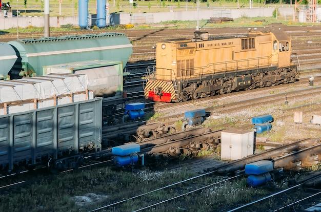 Lokomotywa towarowa sprzęga wagony na stacji kolejowej.