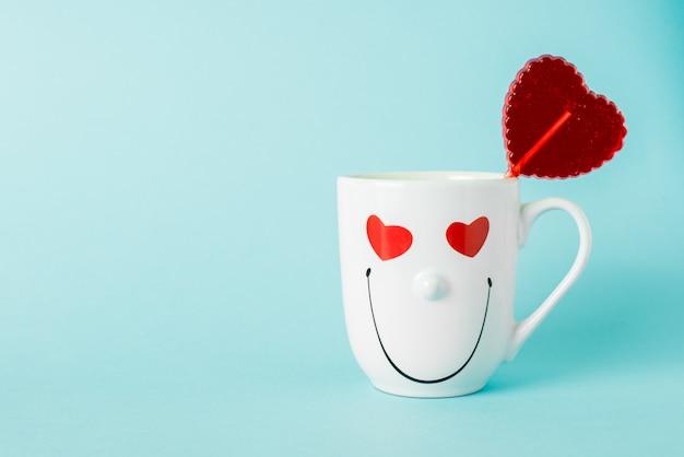 Lollipop w kształcie czerwonego słodkiego serca w kubku o uśmiechniętej twarzy