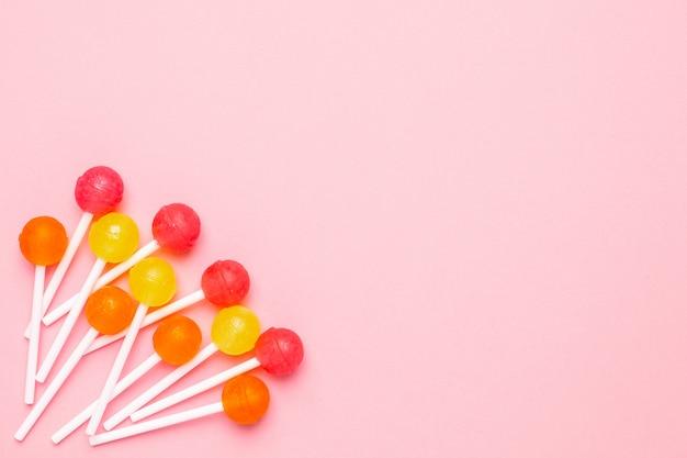 Lollipop w pastelowym różu ze słodkimi różowymi, pomarańczowymi i żółtymi cukierkami. minimalistyczna kompozycja.