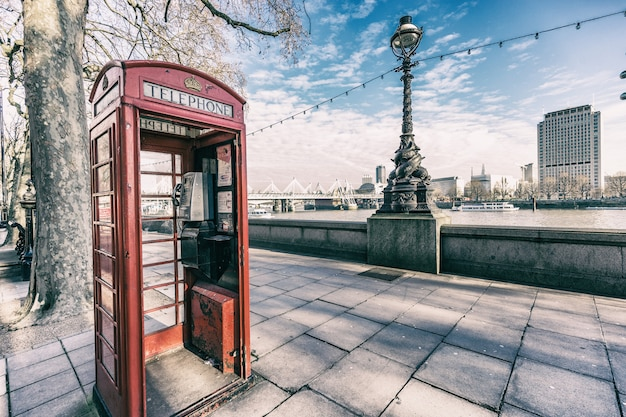 Londyński czerwony budka telefoniczna nad rzeką thames