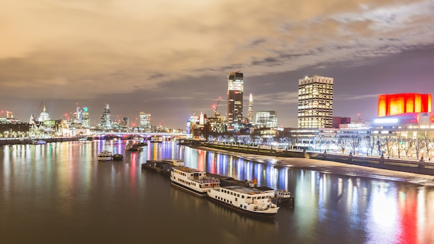 Londyński widok przy nocą z łodziami i drapaczami chmur