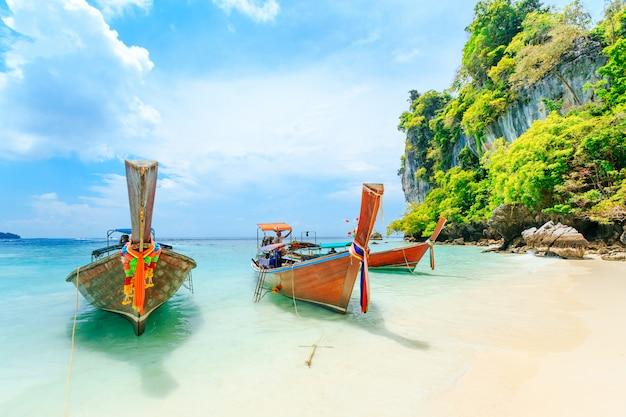 Longtale łódź na plaży przy phuket, tajlandia. phuket jest popularnym miejscem słynącym z plaż.