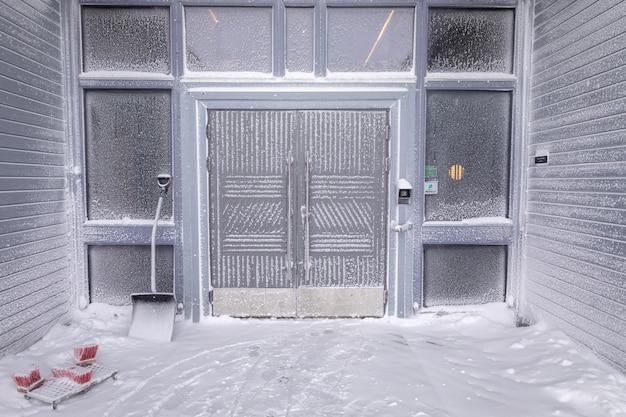 Longyearbyen, svalbard - marzec 2019: wejście do hotelu radisson blu polar spitsbergen pokrytego śniegiem i mrozem