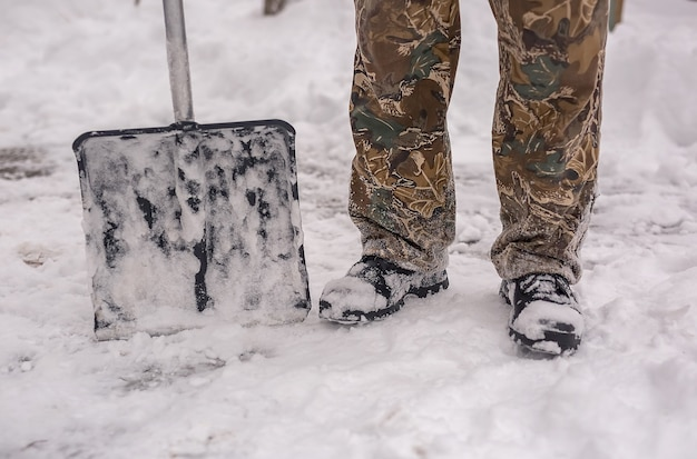 Łopata do odśnieżania stoi u stóp mężczyzny w butach zimowych