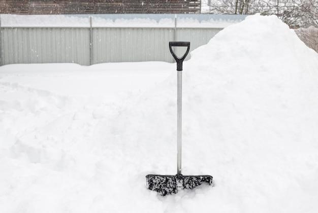 Łopata Do śniegu Stojąca W Głębokim śniegu Na Podwórku Zimowa Pogoda Premium Zdjęcia