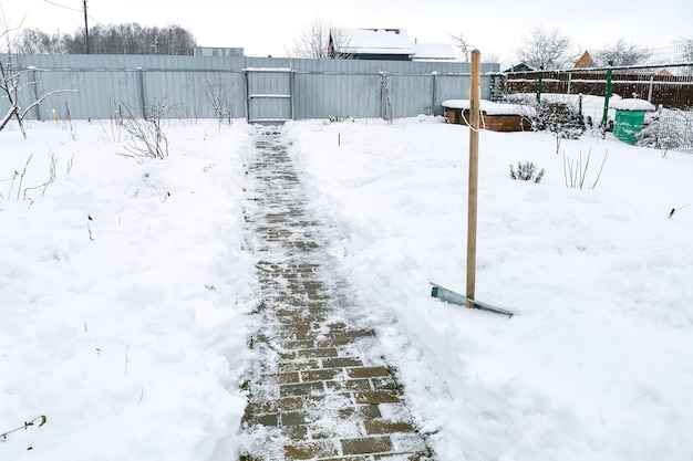 Łopata do śniegu z drewnianą rączką - oczyszczanie ścieżki w zaspie na wiejskiej działce. zimowe obowiązki związane z pielęgnacją wiejskiego domu. prace odśnieżające