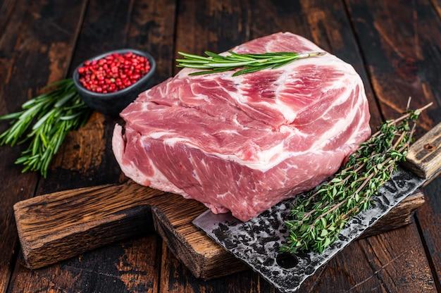Łopatka wieprzowa surowe mięso na świeże steki na drewnianej desce do krojenia z tasakiem rzeźniczym. ciemne drewniane