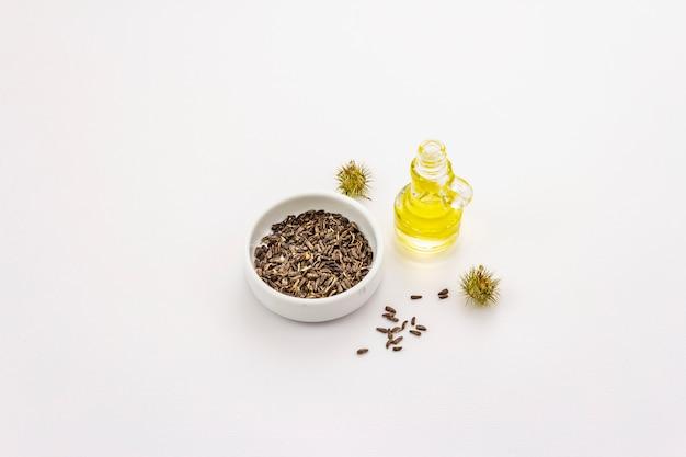 Łopianu olej i ziarna odizolowywający na białym tle. koncepcja pielęgnacji urody i higieny osobistej
