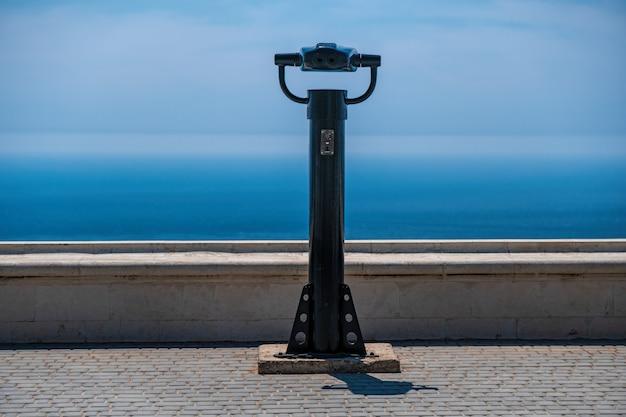 Lornetka na monety i tło błękitnego morza. publiczna lornetka panoramiczna do obserwacji morza.