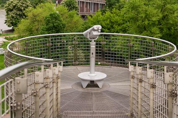 Lornetka na monety, przez teleskop turystyczny, badająca krajobraz.