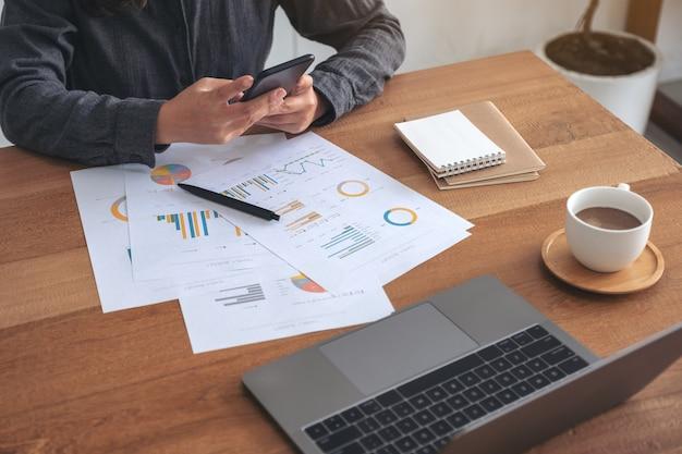 Los przy użyciu telefonu komórkowego podczas pracy nad dokumentem biznesowym i laptopa na stole w biurze