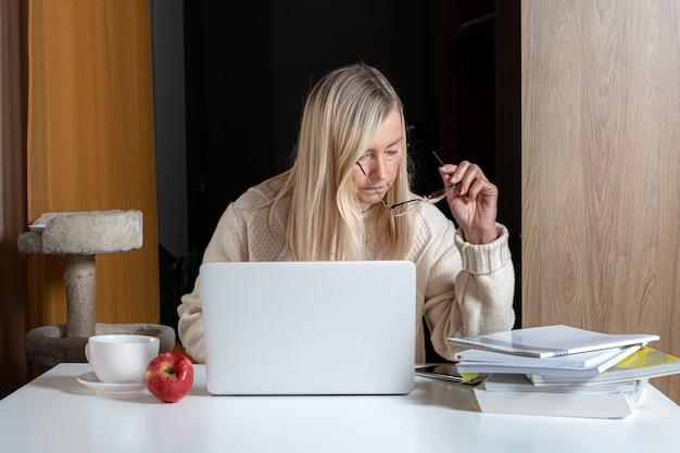 Los w średnim wieku siedzi przy biurku, pracując z dokumentami i laptopem z domowego biura