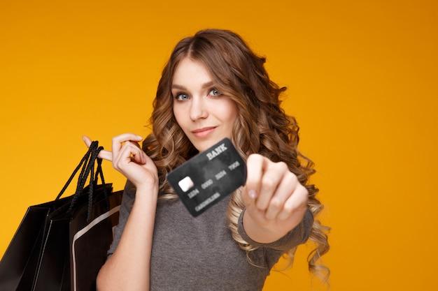 Lose-up portret szczęśliwa młoda kobieta trzyma kartę kredytową i torby na zakupy