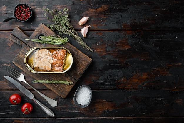 Łosoś, przetwory rybne konserwy rybne wędzone, na desce do krojenia, na starym ciemnym drewnianym stole