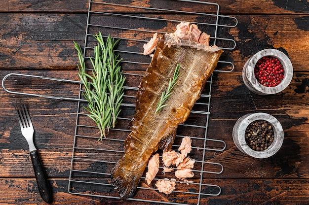 Łosoś ryba wędzona na gorąco na grillu z ziołami. ciemne drewniane tło. widok z góry.