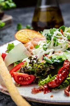 Łosoś wędzony, awokado i sałata, suszone pomidory i sos serowy. zdrowa sałatka. widok z góry
