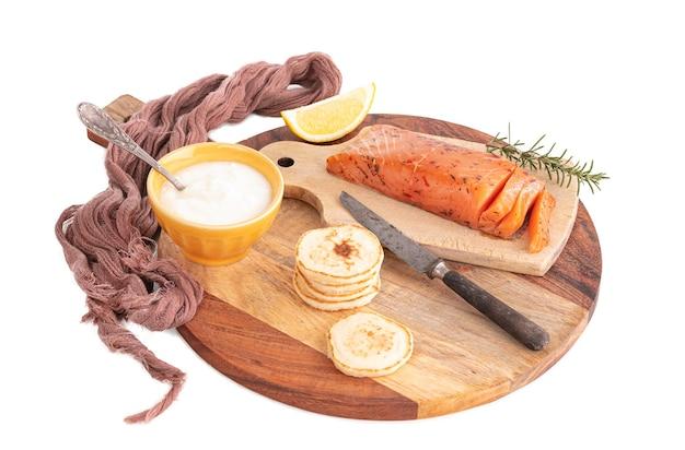 Łosoś wędzony ręcznie na desce do krojenia z blinami i kremem na białej ścianie