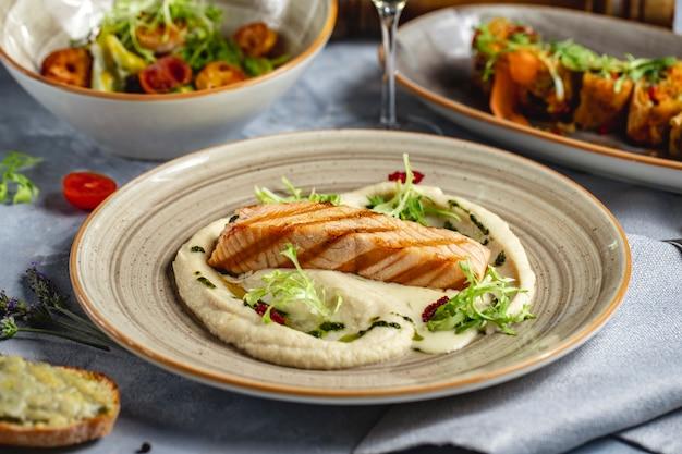 Łosoś z grilla na puree ziemniaczanym z sosem greeens widok z boku