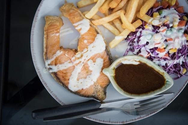 Łosoś z kolorowymi przepisami sałatkowymi w białej płytce na obiad - pojęcie zdrowej żywności.
