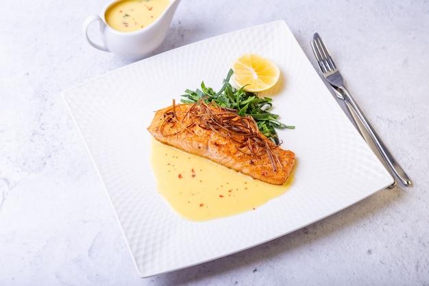 Łosoś z sosem beurre blanc, szpinakiem i cytryną. przyozdobiony porami. tradycyjne danie francuskie. zbliżenie.