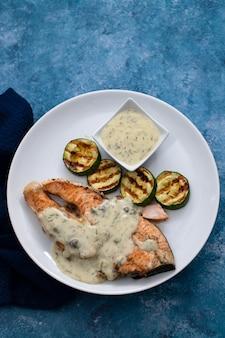 Łosoś z sosem i grillowanymi warzywami na białym talerzu