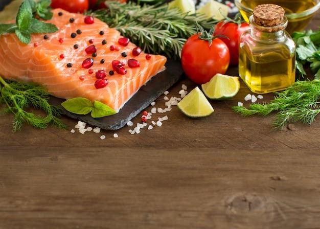 Łosoś z warzywami, oliwą z oliwek i ziołami na drewnie z bliska z miejsca na kopię