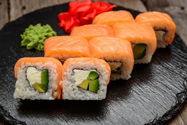 Łososiowe sushi rolki na kamieniu wsiadają