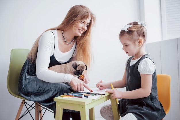 Losowania matki i córki są zaangażowane w kreatywność w przedszkolu. mały mops z nimi